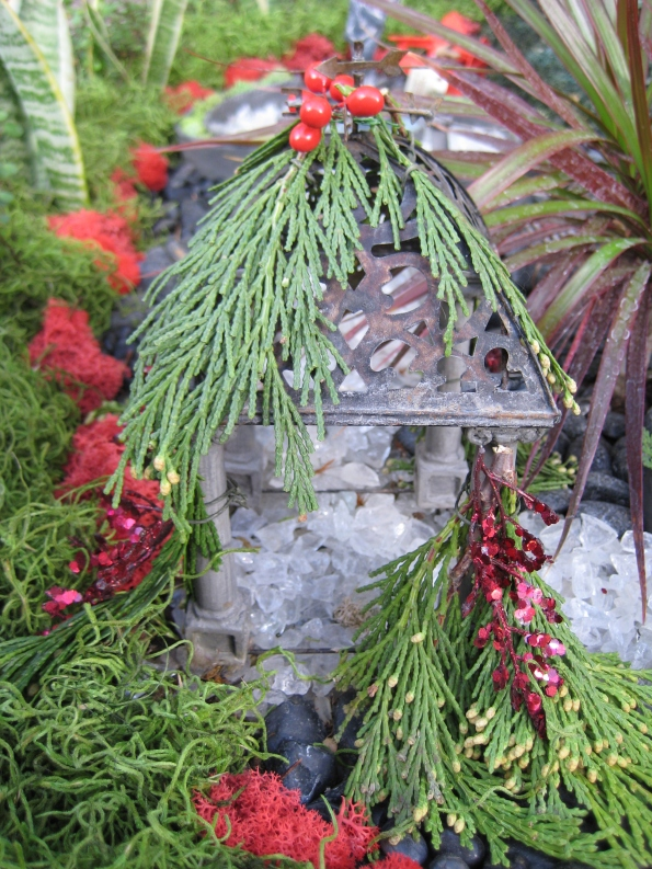Miniature gazebo decorated with greens and bling