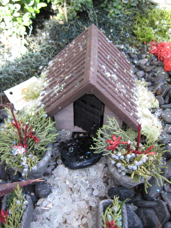 Miniature fairy house with spruce tip pots