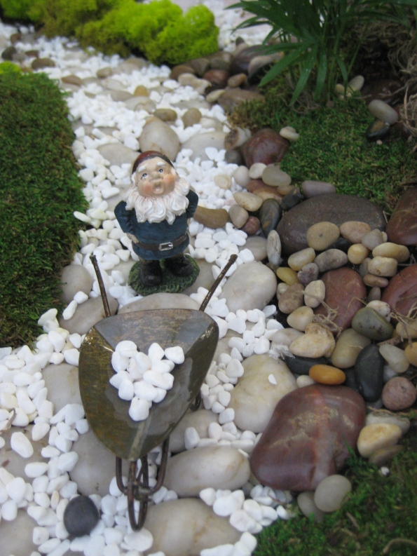 Gnome on a path with his wheelbarrow  full of stones